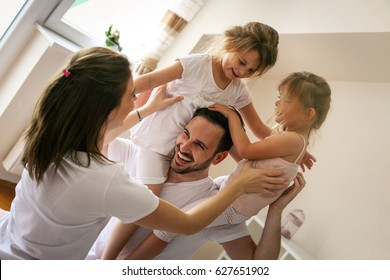 Cheerful family playing together on bed. Parents spending free time with their daughters. Daughters sitting on fathers shoulders.
