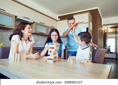 A cheerful family plays board games at home.