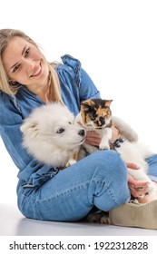 Cheerful family portrait consisting of young woman, samoyed puppy and cat