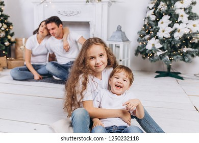 Cheerful family portrait have a happy christmas and new year in cozy home with christmas lights and holiday decorations