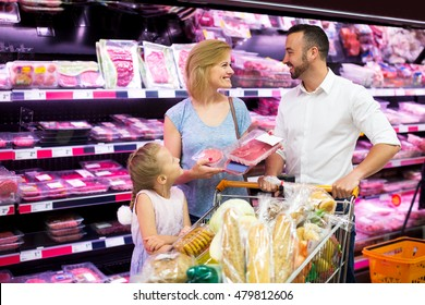 Cheerful family shopping various fresh red meat in supermarket