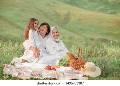 Cheerful family sitting on the grass during a picnic in a park, there is a basket with meal