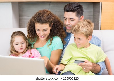 Cheerful family sitting on sofa with laptop shopping online at home in living room