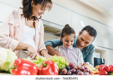cheerful family slicing fruits and vegetables together at kitchen