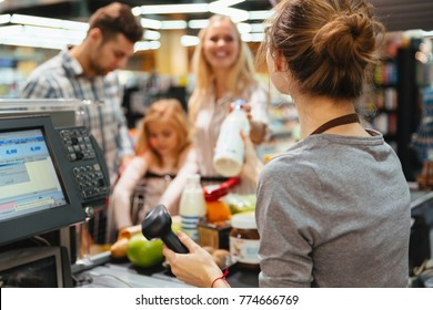 Cheerful family standing at the cash counter buying groceries at the supermarket
