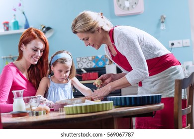 A cheerful family of three girls having fun while making pastry in a kitchen full of color