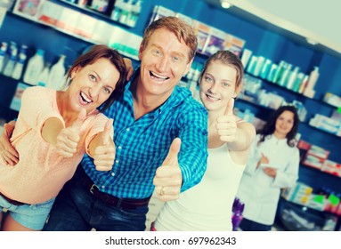 Cheerful family of three persons holding thumbs up in pharmacy among shelves with goods