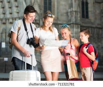 Cheerful family of tourists with two children looking for destination with city map