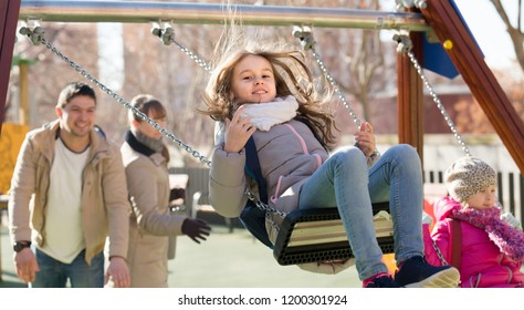 Cheerful family with two girls having fun on swings outdoors