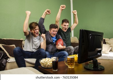Cheerful family watching Superbowl with hands in the air  /  touchdown