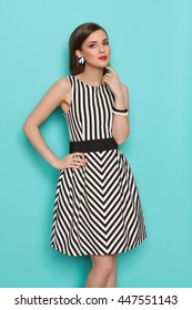 Cheerful fashion model in striped dress posing with hand on hip. Three quarter length studio shot on turquoise background.