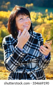 Cheerful fashion woman 40 years old wearing warm clothes in autumn. Beautiful brunette with autumn coat. Smiled and writing sms on her smartphone, Gold autumn background