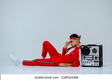 cheerful fashionable man wearing a red sports suit sitting with a retro tape recorder. proud and successful style of the 90's.
