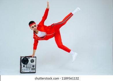 cheerful fashionable man wearing a red sports suit dancing jumps with a retro tape recorder. interesting and fervent style of the 90s.