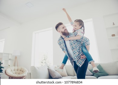 Cheerful father carrying on back little playful joyful kid with raised fist celebrating victory in game, family with one parent spending time in modern house with interior, babysitting concept