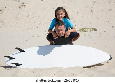 Cheerful father and her daughter on holidays with surf