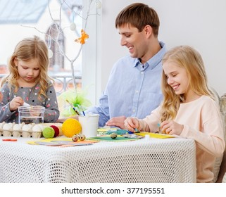 Cheerful father and his daughters painting and decorating easter eggs.