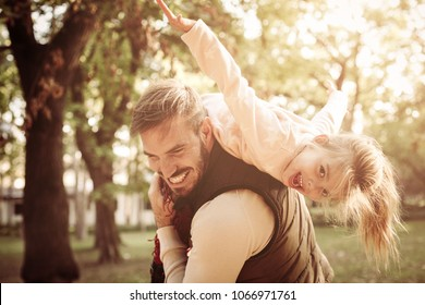 Cheerful father holding his daughter on shoulders and playing together