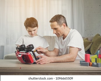 Cheerful father is repairing toy vehicle of his son. Child is watching how parent using tool with interest