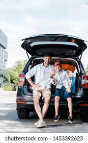cheerful father sitting near son with wooden biplane near car
