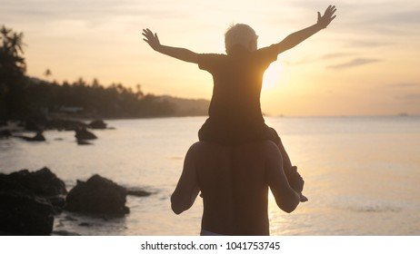 Cheerful father and son in eyeglasses spend happy time playing on tropical beach at beautiful sunset.