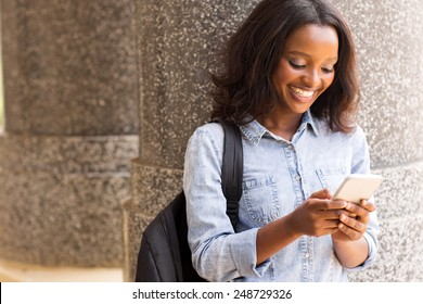cheerful female afro american university student using cell phone