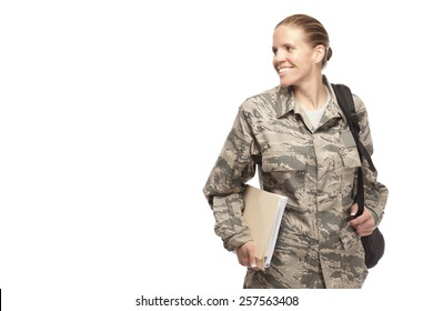Cheerful female airman with books and bag and looking away