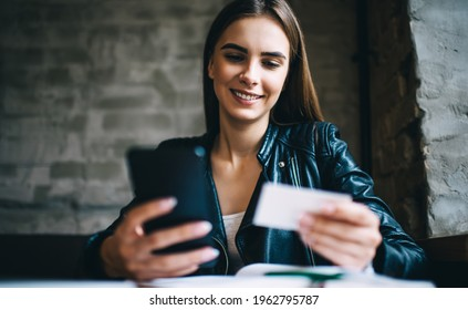 Cheerful female checking contact on white business card for dialing number on modern cellphone technology, happy Caucasian student reading text on paper with information for mobile calling