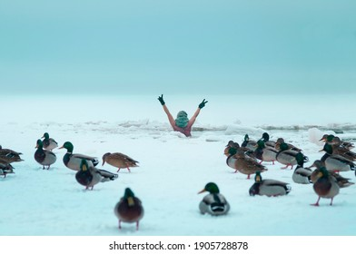Cheerful female in the cold water, with a naked torso ad hands up among the snowdrifts, ice floes and falling snow. Ducks sitting around the lake on the ice suface