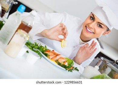 Cheerful female cook with plate of  prepared shrimps in restaurant
