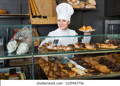 Cheerful female cooks demonstrating and selling to the customer pastry in the cafe counter