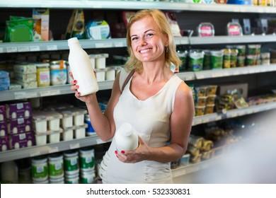 cheerful female customer choosing milk from refrigerator indoors
