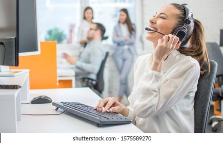 Cheerful female customer services agent with headset working in call center