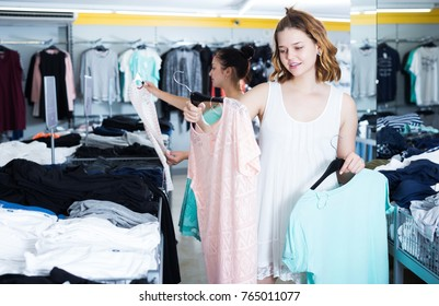 Cheerful female customers looking for new garments at the store
