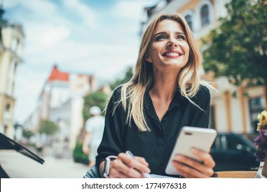 Cheerful female with cute smile on face holding cellular device for browser networking enjoying leisure in city, prosperous hipster blogger feeling carefree happiness and delight from mobility