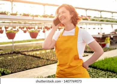 Cheerful female farmer smiling and answering phone call while standing inside hothouse