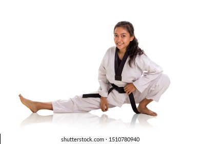 Cheerful female fighter doing physical training, stretches her right leg straight during warm up. Studio shot, portrait over white background