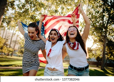 Cheerful female friends running around the park with American flag. Young and enthusiastic American girls enjoying 4th of july holiday at park.