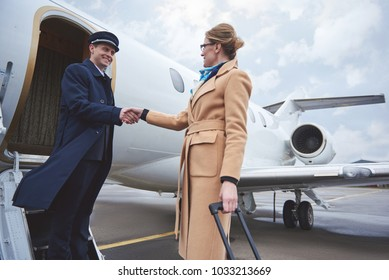 Cheerful female greeting with beaming aviator on street. Journey concept