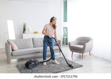 Cheerful female housekeeper using vacuum cleaner to tidy apartment, full length portrait. Positive young woman doing house chores, keeping her home clean. Domestic hygiene concept