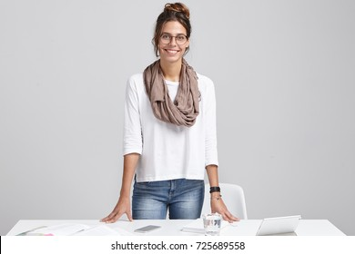 Cheerful female interior designer in glasses, stands at her workplace, places hands on desk after finished working on new project, expressing pleasant emotions as achieves great results and goals