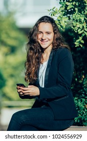 Cheerful female intern using gadget outdoors