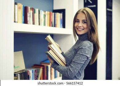 Cheerful female international student putting in order books returned after reading for literature lesson standing near bookshelves in modern interior library of university during break between lesson