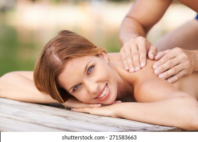 Cheerful female looking at camera while enjoying procedure of massage