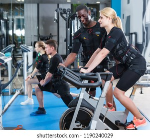 Cheerful female and male athletes in EMS suit exercising in modern gym