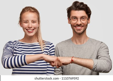 Cheerful female and male partners give fist bump, demonstrates their agreement, have broad smiles on faces, rejoice success and cooperation, have good relationship, isolated on white background
