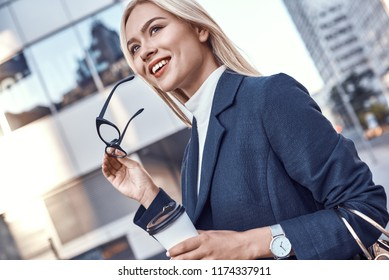Cheerful female manager getting to work by foot drinking morning coffee to go while walking street, successful businesswoman in elegant wear enjoying sunny weather