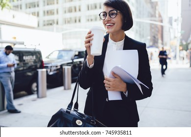 Cheerful female manager getting to work by foot drinking morning coffee to go while walking street, successful businesswoman in elegant wear enjoying sunny weather strolling with papers and documents