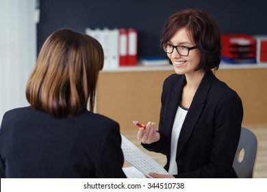 Cheerful Female Manager Talking to her Subordinate at her Table Inside the Office.