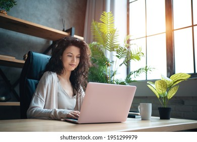 cheerful female manager working with laptop and typing at home office